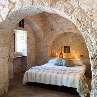 Idee per una camera matrimoniale mediterranea con pavimento in cemento, nessun camino e pavimento grigio