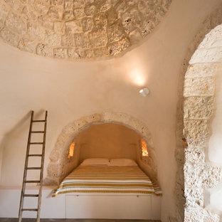 На фото: маленькие гостевые спальни в средиземноморском стиле с бежевыми стенами, бетонным полом и серым полом без камина