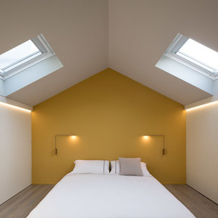 This is an example of a contemporary master bedroom in Milan with medium hardwood floors, brown floor and yellow walls.