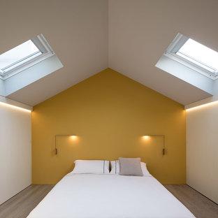 Foto di una camera matrimoniale design con pavimento in legno massello medio, pavimento marrone e pareti gialle