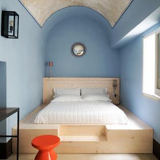 Immagine di una camera da letto mediterranea con pareti blu, nessun camino e pavimento beige