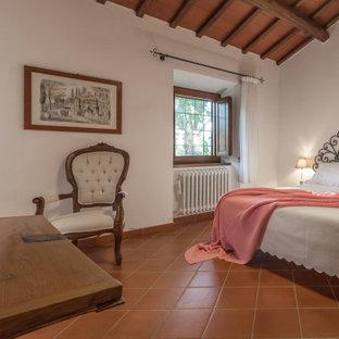 Foto di una camera da letto mediterranea con pareti bianche e pavimento marrone