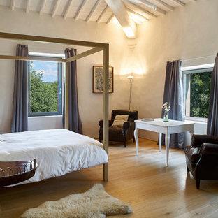 Esempio di una camera matrimoniale boho chic di medie dimensioni con pavimento in legno massello medio, pareti beige e pavimento marrone