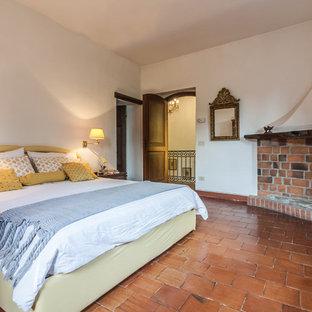Esempio di una camera matrimoniale classica con camino ad angolo, pareti bianche, pavimento in terracotta, cornice del camino in mattoni e pavimento marrone