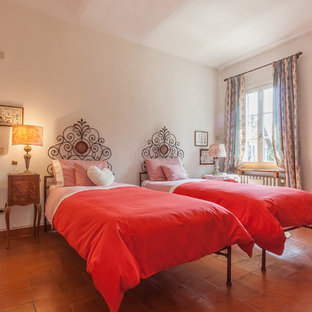 Design ideas for a traditional guest bedroom in Other with white walls, terra-cotta floors and brown floor.