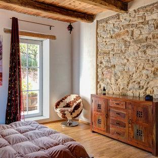 Immagine di una camera degli ospiti mediterranea di medie dimensioni con pareti bianche, pavimento in legno massello medio e pavimento marrone