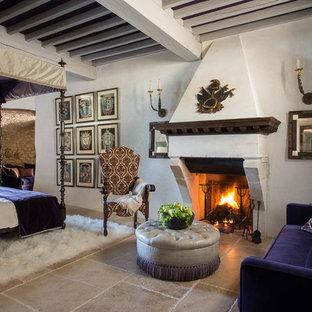 На фото: большая хозяйская спальня в классическом стиле с белыми стенами, полом из известняка, стандартным камином и фасадом камина из камня с