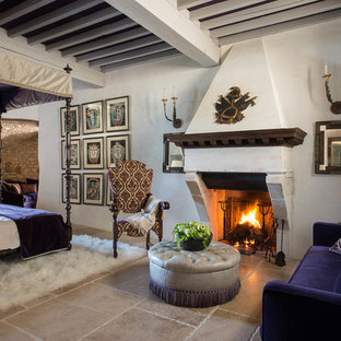 Inspiration for a large timeless master limestone floor bedroom remodel in Florence with white walls, a standard fireplace and a stone fireplace