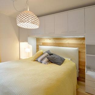 Aménagement d'une chambre contemporaine avec un mur blanc, un sol en bois clair et un sol beige.