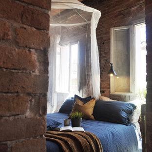 Foto di una camera da letto industriale con pareti rosse, pavimento multicolore, travi a vista, soffitto in legno e pareti in mattoni