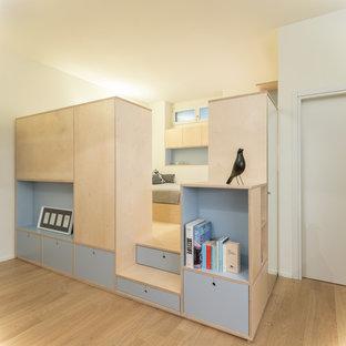 Esempio di una camera da letto stile loft contemporanea di medie dimensioni con pareti bianche, parquet chiaro e pavimento beige