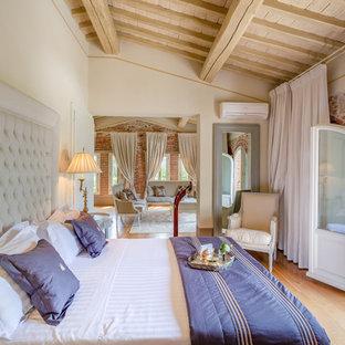 Foto di una camera da letto tradizionale con pareti beige, parquet chiaro e pavimento beige