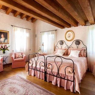 Esempio di una camera da letto chic con pareti bianche, pavimento in legno massello medio e pavimento marrone