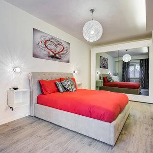 Стильный дизайн: маленькая хозяйская спальня в современном стиле с белыми стенами и полом из ламината - последний тренд