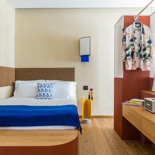 Ispirazione per una grande camera da letto minimal con pareti beige, pavimento in legno massello medio e pavimento marrone