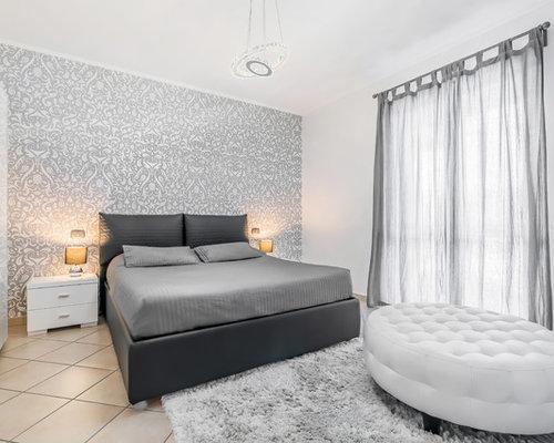 Camera da letto contemporanea con pavimento con piastrelle in ...
