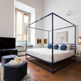 Ispirazione per una camera da letto design con pareti bianche, pavimento in terracotta e pavimento rosso