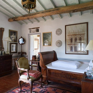 Country bedroom in Florence with white walls and terra-cotta floors.