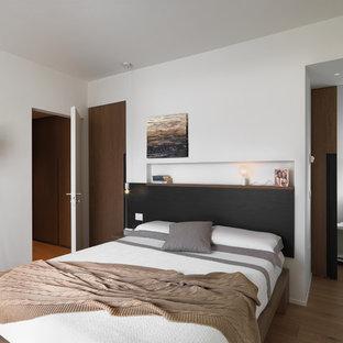 Foto di una camera da letto design con pareti bianche, parquet chiaro e pavimento marrone