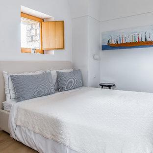 Ispirazione per una camera da letto mediterranea con pareti bianche e nessun camino