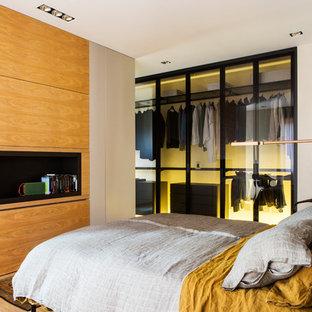 Foto di una camera matrimoniale design di medie dimensioni con pareti bianche, nessun camino e pavimento marrone