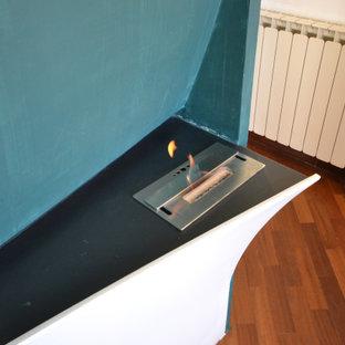 Immagine di una piccola camera matrimoniale design con pareti bianche, parquet scuro, camino sospeso, cornice del camino in intonaco e travi a vista