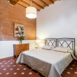 Photo of a rural bedroom in Florence with red walls, terracotta flooring and red floors.