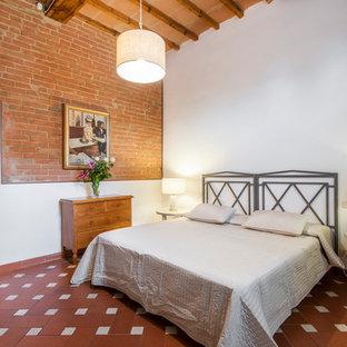 Esempio di una camera da letto country con pareti rosse, pavimento in terracotta e pavimento rosso