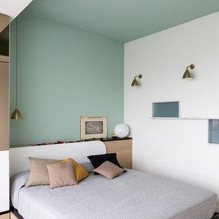 Esempio di una camera matrimoniale minimal con pareti verdi, parquet chiaro e pavimento marrone