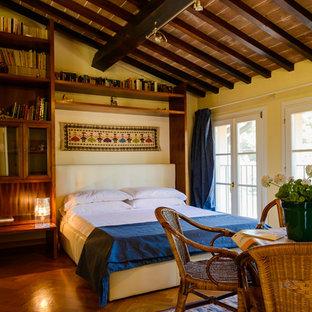Esempio di una camera da letto mediterranea con pareti gialle, pavimento in legno massello medio e pavimento marrone