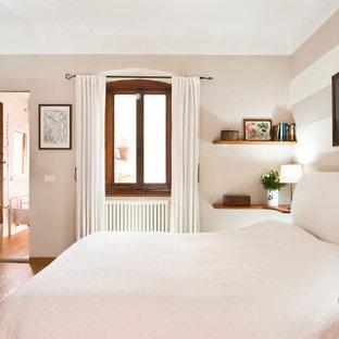 Modelo de dormitorio principal, romántico, pequeño, con paredes blancas, suelo de madera clara, chimenea tradicional, marco de chimenea de piedra y suelo marrón