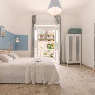 Ispirazione per una camera matrimoniale costiera con pareti bianche e pavimento grigio