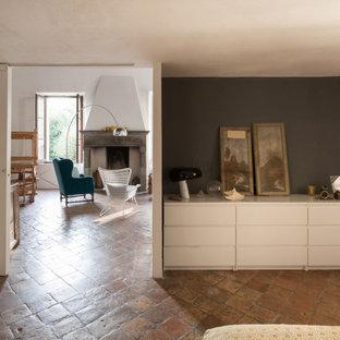 Geräumiges Stilmix Hauptschlafzimmer mit grauer Wandfarbe, Backsteinboden, Kamin, Kaminumrandung aus Stein und freigelegten Dachbalken