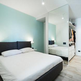 Foto di una camera matrimoniale minimal con pareti blu, parquet chiaro e pavimento beige