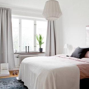 Esempio di una camera da letto scandinava con pareti bianche, pavimento in legno massello medio e pavimento marrone