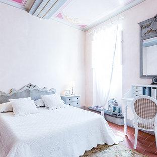 Medelhavsstil inredning av ett sovrum, med beige väggar och klinkergolv i terrakotta
