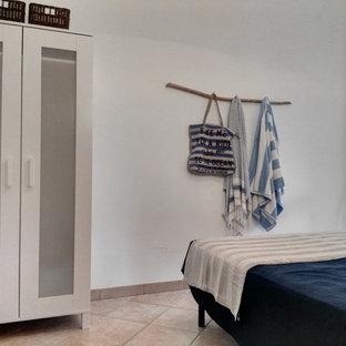 Ejemplo de habitación de invitados rústica, pequeña, con paredes blancas, suelo de baldosas de cerámica y suelo rosa
