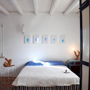 Idéer för ett medelhavsstil sovrum, med vita väggar och tegelgolv