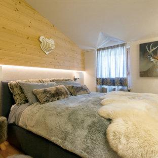 Foto di una camera matrimoniale rustica con pavimento in legno massello medio e pareti bianche