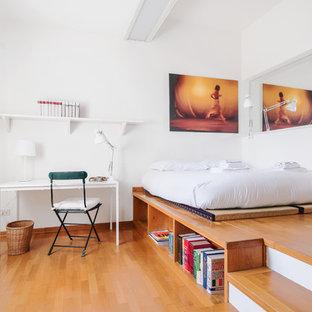 Immagine di una camera matrimoniale design con pareti bianche e pavimento in legno massello medio