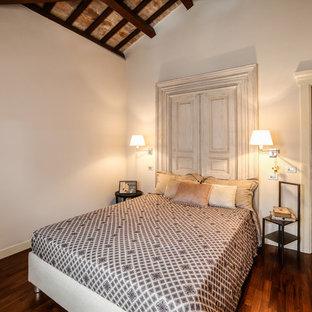 Esempio di una camera matrimoniale mediterranea con parquet scuro, pavimento marrone e pareti beige