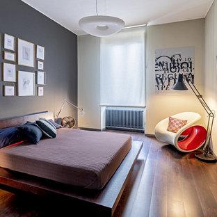 Esempio di una camera da letto contemporanea con pareti grigie, pavimento in legno massello medio e pavimento marrone