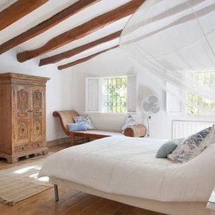 Modelo de dormitorio principal, campestre, grande, con paredes blancas y suelo de ladrillo