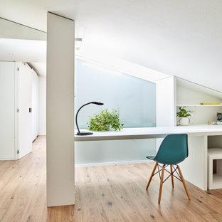 他の地域の小さいコンテンポラリースタイルのおしゃれな寝室 (白い壁、ラミネートの床、茶色い床) のインテリア