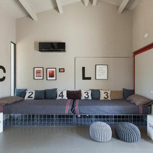 Exemple d'une chambre mansardée ou avec mezzanine scandinave de taille moyenne avec un mur beige, béton au sol et un sol gris.