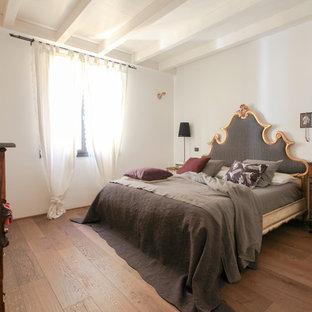Foto di una camera matrimoniale mediterranea con pareti bianche, parquet scuro e pavimento marrone