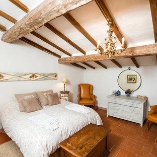 Immagine di una camera matrimoniale country di medie dimensioni con pareti bianche, pavimento in terracotta e pavimento marrone