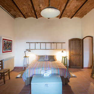Mid-sized country master brick floor and brown floor bedroom photo in Other with white walls