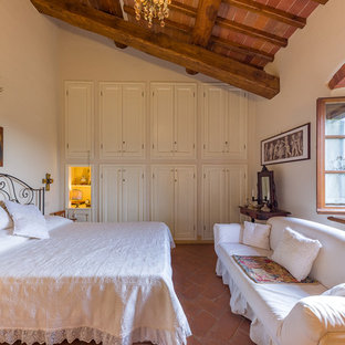 Example of a tuscan terra-cotta floor and red floor bedroom design in Florence with beige walls