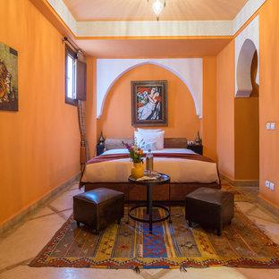 Esempio di una camera degli ospiti mediterranea con pareti arancioni e pavimento beige